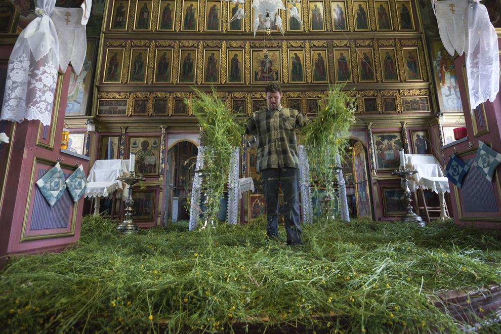 """Simion, clopotarul bisericii """"Sfânta Treime"""", împrăştie iarba în interiorul lăcaşului de cult. Acest ritual simbolizează apropierea enoriaşilor de Grădină Raiului, locul păcatului originar şi acolo unde s-a pogorât pentru prima dată Duhul Sfânt."""