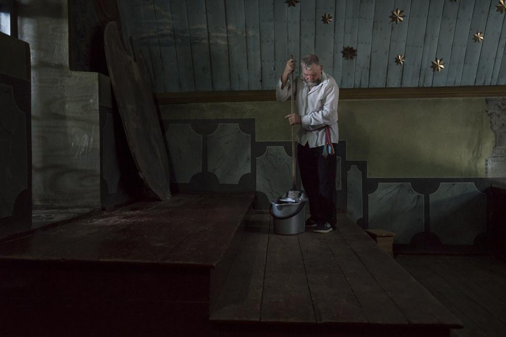 """Ivan Cozma, 68 de ani, spala podelele în biserica """"Sfânta Treime"""", construită în jurul anului 1833, acolo unde se va ţine slujba de Rusalii."""