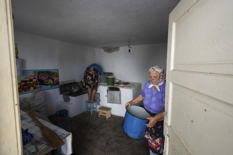 Femeile din sat spală vasele în care au făcut mâncarea pentru masa de după slujba de Rusalii.