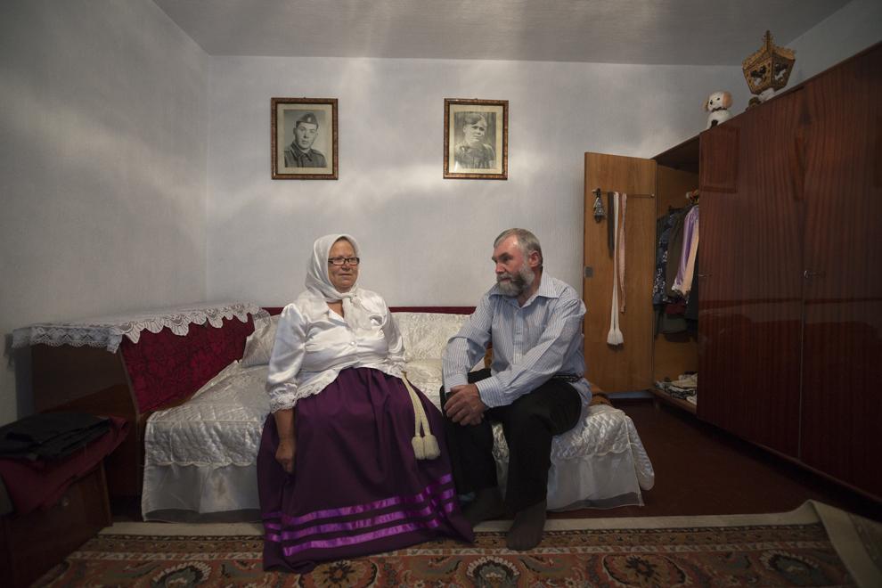 """Fiocla Cozma, 64 de ani, şi Ivan Cozma, 68 de ani, sunt îmbrăcaţi cu haine tradiţionale lipoveneşti şi se pregătesc să meargă la slujba de Rusalii, ţinută în biserica """"Sfântă Treime"""". Pe uşă şifonierului se pot vedea mai multe brâuri tradiţionale, numite """"pois""""."""