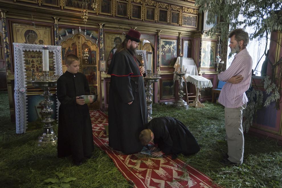 Un copil de altar îngenunchează în faţa Înalt Prea Sfinţiei sale, Arhiepicopul Flavian al Slavei.