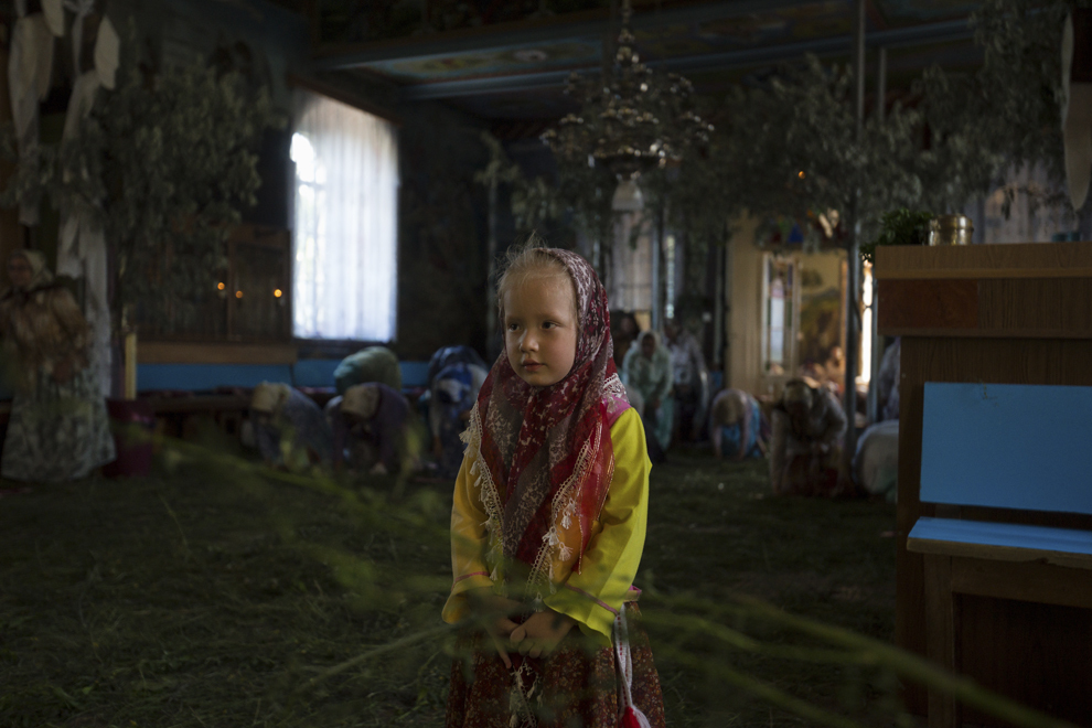 """Iulia, 4 ani, asistă la slujba de Rusalii, ţinută în biserica """"Sfântă Treime""""."""
