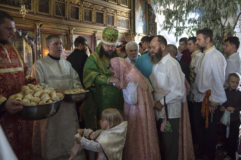 Enoriaşii săruta mâna Înalt Prea Sfinţiei sale, Arhiepicopul Flavian al Slavei, înainte de a lua prescură la slujba de Rusalii. Veşmântul de culoare verde simbolizează viaţa veşnică a credincioşilor.