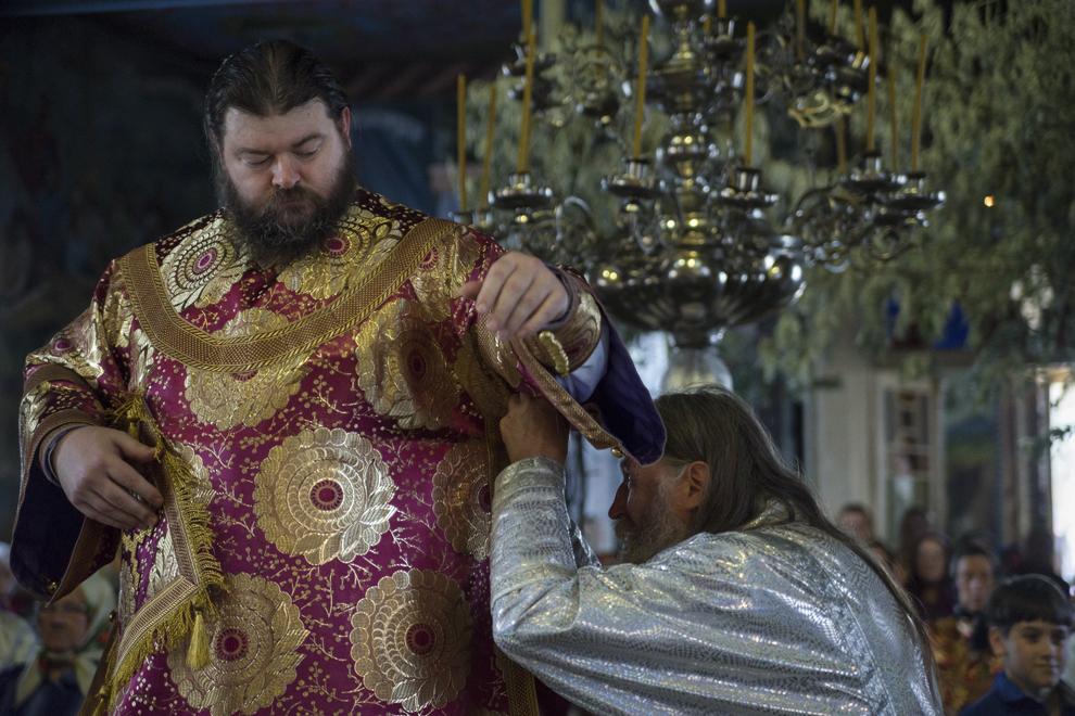 Înalt Prea Sfinţia sa, Arhiepicopul Flavian al Slavei, este îmbrăcat în veşmintele arhiereşti, făcute special pentru el cu ocazia slujbei de Rusalii.
