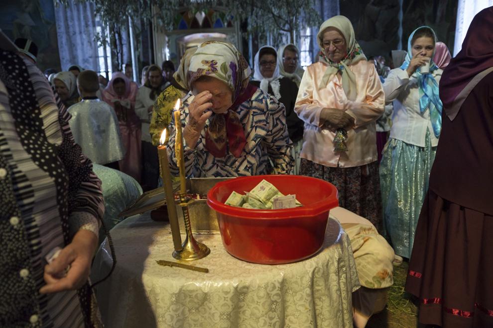 """O femeie se închină în faţa unei icoane vechi, în timpul slujbei de Rusalii, ţinută în biserica """"Sfântă Treime""""."""