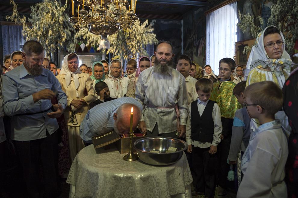 """Un bărbat se închină în faţa unei icoane vechi, în timpul slujbei de Rusalii, ţinută în biserica """"Sfântă Treime""""."""