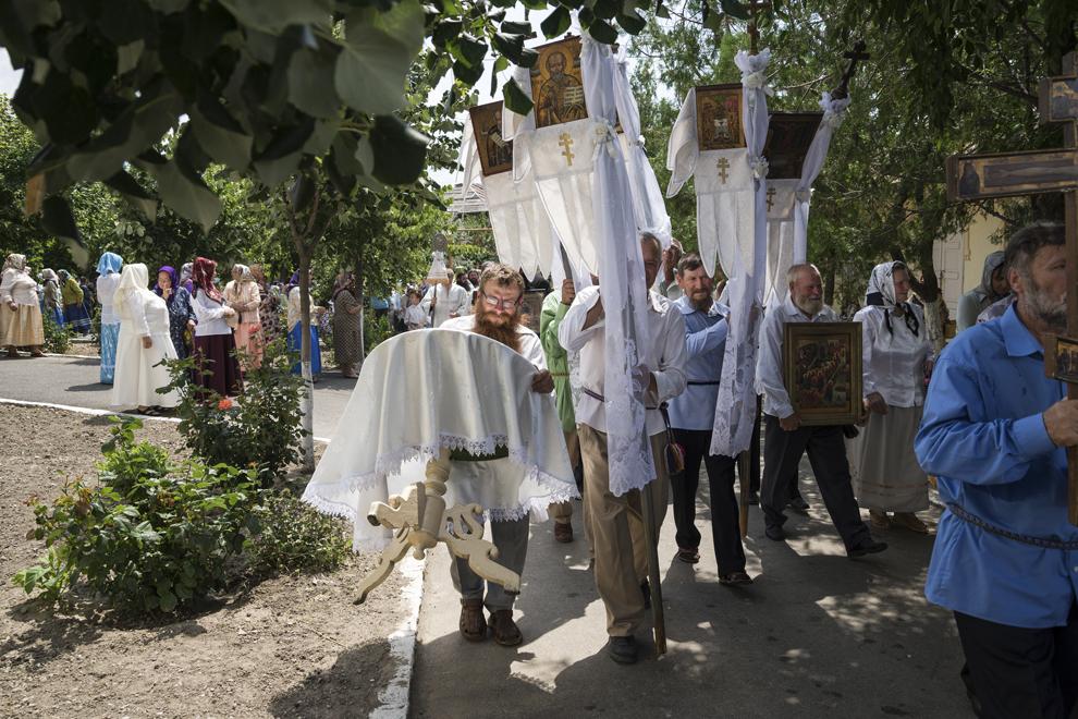 """Enoriaşii, purtând icoane în mâini, înconjoară Biserica """"Sfântă Treime"""", tradiţie aferentă slujbei de Rusalii."""