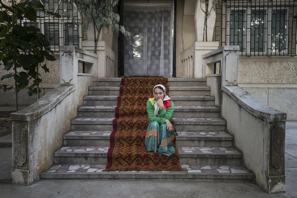 """O fată se odihneşte după câteva ore de stat în picioare la slujba de Rusalii, ţinută în biserica """"Sfântă Treime""""."""