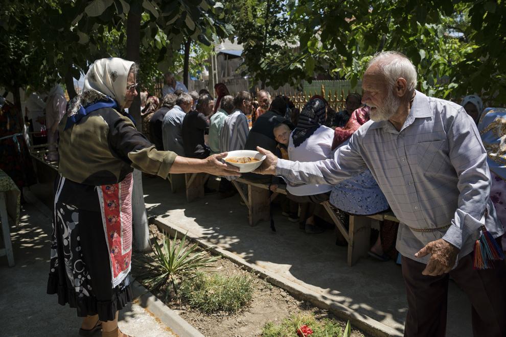 """Enoriaşii mănâncă după terminarea slujbei de Rusalii, ţinută în biserica """"Sfântă Treime""""."""