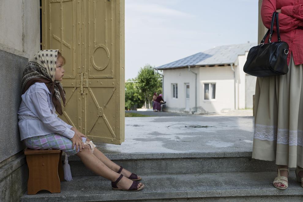 O fetiţă priveşte către mama ei, după terminarea slujbei de Rusalii.