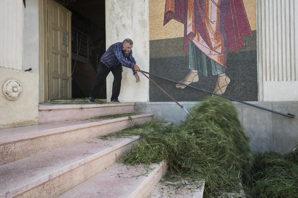 """Ivan Cozma, 68 de ani, înlătura iarba din Biserica """"Sfântă Treime"""", la sfârşitul slujbei de Rusalii."""