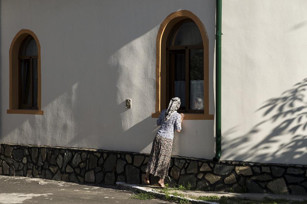 """Natalia Pavel, soţia preotului Vasile, se uită pe geamul bisericii mici, """"Sfântul Nicolae"""", pentru a vedea dacă s-a terminat slujba."""