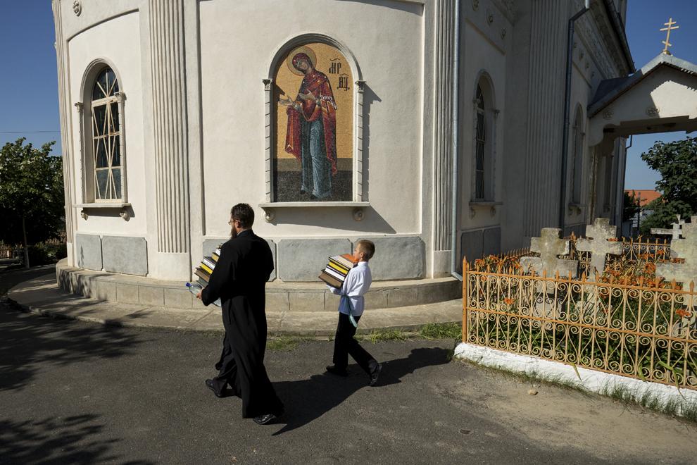 """Simionovici Lavrente, dascăl, şi Antonio Petrehov, duc carţile sfinte din biserica mică, """"Sfântul Nicolae"""", în cea mare, """"Sfânta Treime""""."""