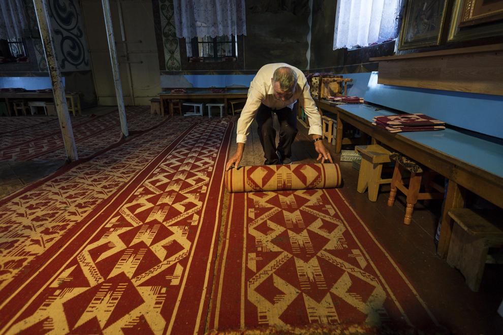 """Ivan Cozma, 68 de ani, începe curăţenia, strângând covoarele, în biserica mare, """"Sfânta Treime"""", construită în jurul anului 1833, acolo unde se ţine slujba de Rusalii."""