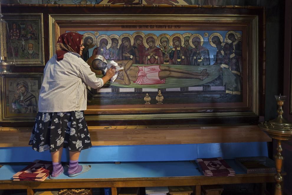 """Fiocla Cozma, 64 de ani, şterge o icoană din biserica """"Sfânta Treime"""", care-l înfăţişează pe Iisus înainte de a fi înmormântat."""