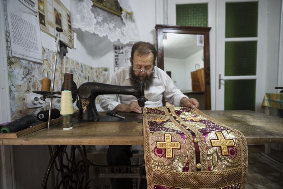 Croitorul Saveli termină de făcut straiele arhieresti pentru Înalt Prea Sfinţia Sa Arhiepiscopul Flavian al Slavei, pe care acesta din urmă le va îmbrăca în Duminca Rusaliilor.