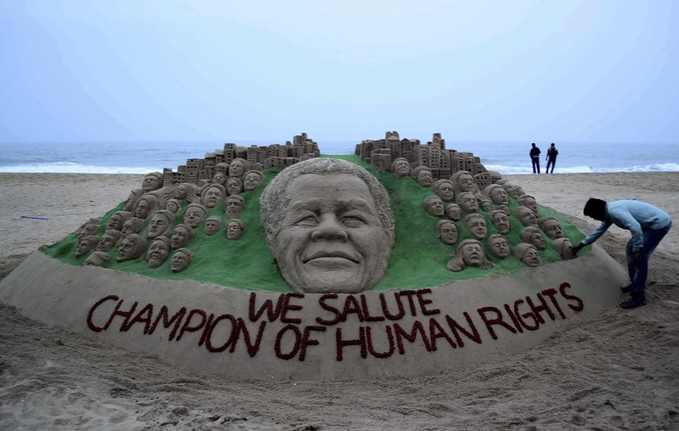 Artistul indian Sudarsan Pattnaik lucrează la o sculptură de nisip înfăţişându-l pe fostul preşedinte sud african, Nelson Mandela, pe plaja Puri din India, luni, 9 decembrie 2013.