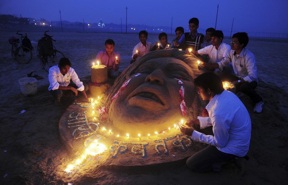 Studenţi lucrează la o sculptură de nisip în semn de omagiu, în timpul comemorării primei aniversări a unui viol fatal în grup întâmplat unei studente de 23 de ani din New Delhi, în Allahabad, luni, 16 decembrie 2013.
