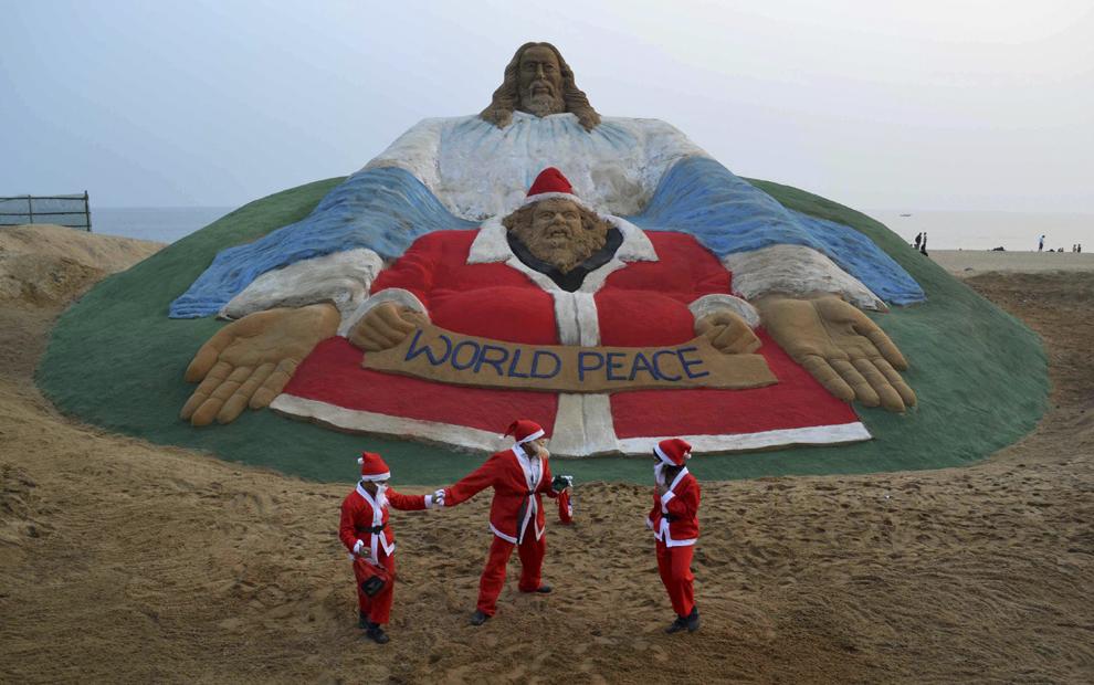 Copii îmbrăcaţi în costume de Moş Crăciun se joacă lângă o sculptură de nisip reprezentându-i pe Isus Hristos şi Moş Crăciun, creată  de artistul Sudarsan Pattnaik pe plaja Golden Sea din Puri, India, marţi, 24 decembrie 2013.