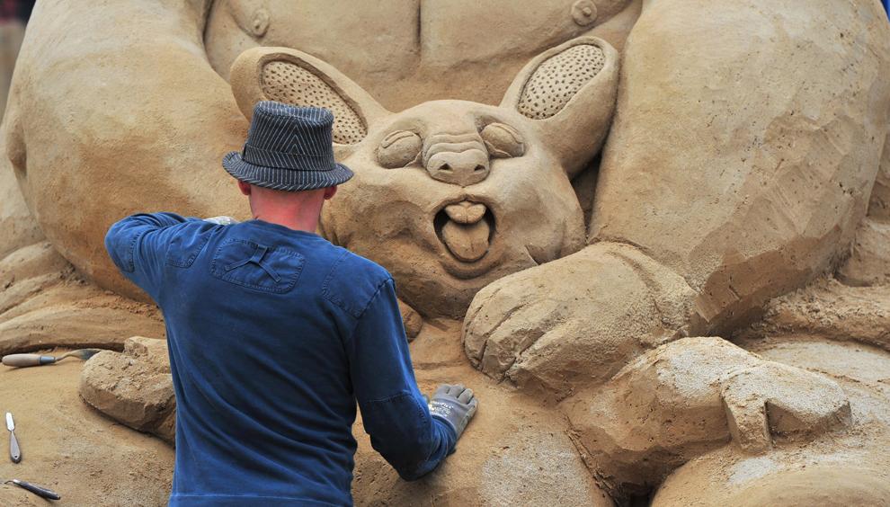 Un bărbat lucrează la sculptura sa de nisip în timpul festivalului Sandstation, în Berlin, Germania, luni, 7 iunie 2010.