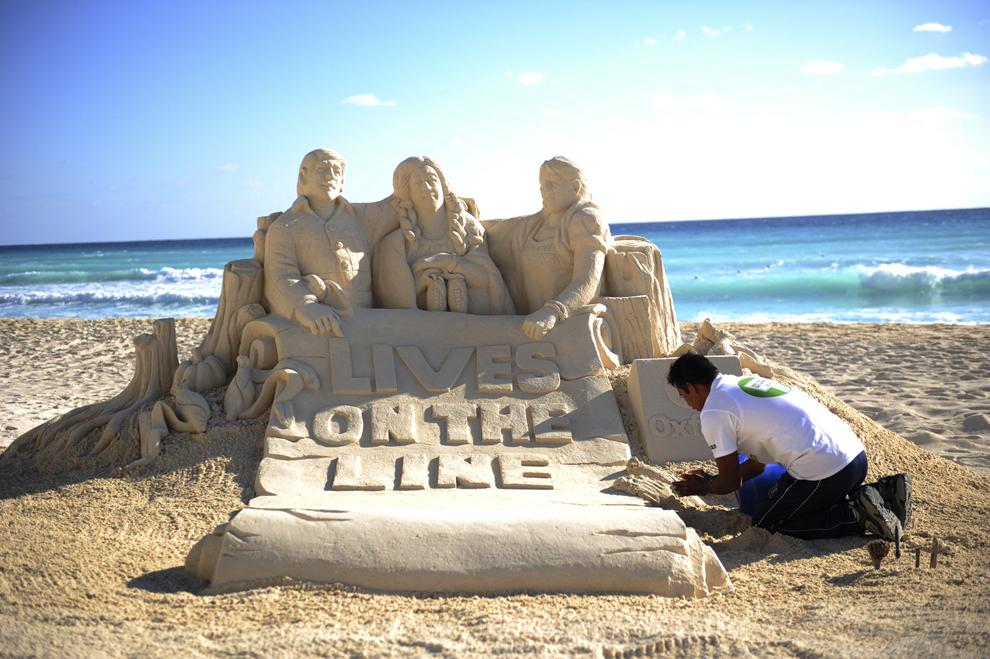 Un activist de la fundaţia de caritate Oxfarm, lucrează la o sculptură de nisip pe o plajă din Cancun, Mexic, vineri, 10 decembrie 2010.
