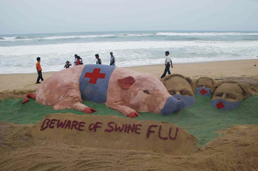 """Persoane trec pe lângă o sculptură înfăţişând un porc ce poartă o mască chirurgicală cu mesajul """"Feriţi-vă de gripa porcină"""", creată de artistul Sudersan Pattnaik, pe plaja Puri din India, joi, 18 iunie 2009."""