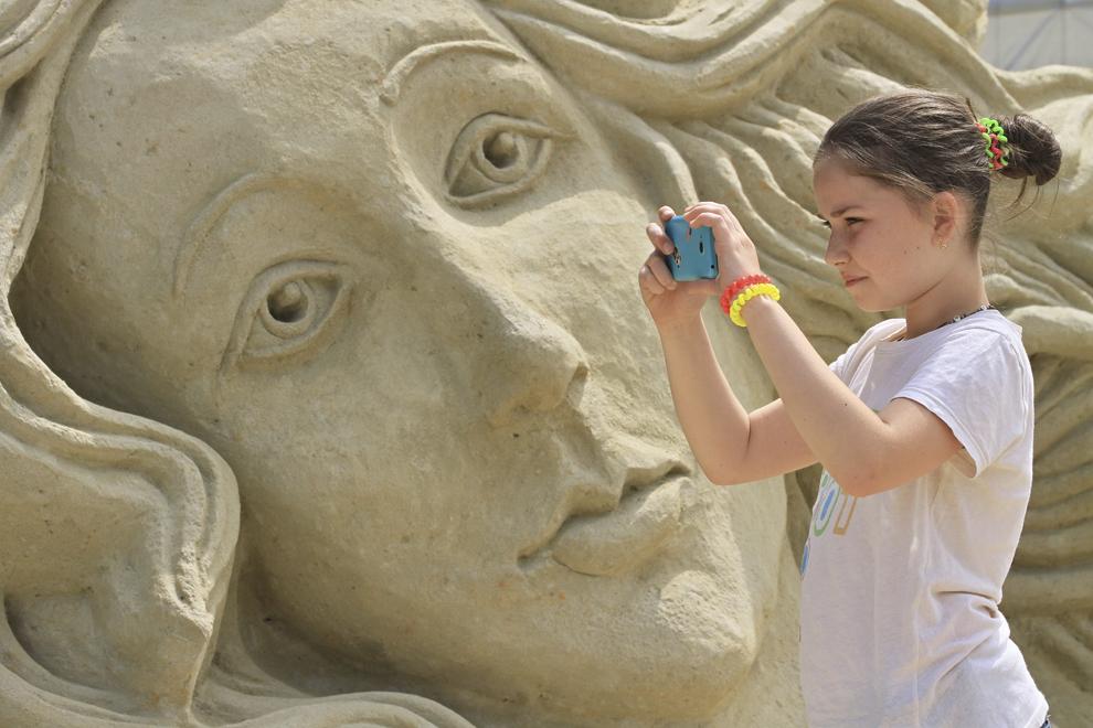 """O fetiţă face o fotografie cu telefonul mobil, lângă o sculptură de nisip intitulată """" Botticelli Venus"""" în timpul festivalului de nisip, în Lednice, Moravia, joi, 19 iunie 2014."""