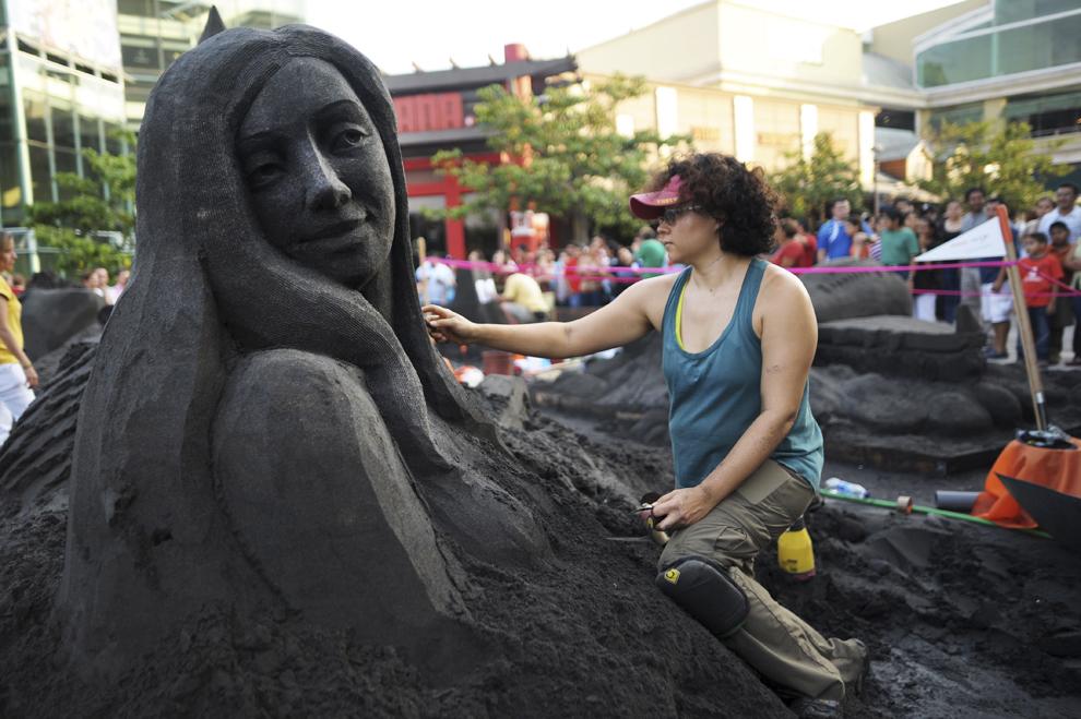 """O femeie lucrează la o sculptură în nisip, în timpul festivalului """"Nisip în Oraş"""" în San Salvador, sâmbătă, 13 aprilie 2013."""