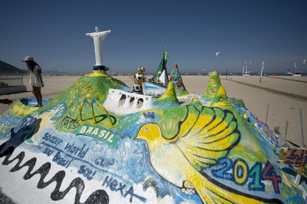 """O tânără stă lângă o sculptură în nisip intitulată """"Brazil World Cup Fifa 2014"""" pe plaja Copacabana din Rio de Janeiro, vineri, 2 mai 2014."""