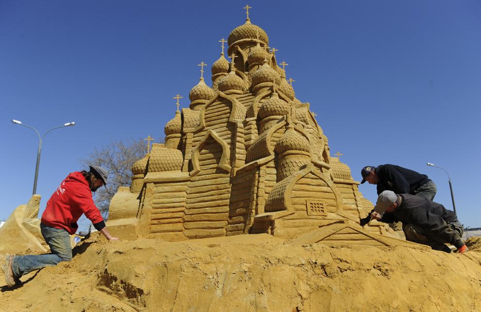 Trei bărbaţi lucrează o sculptură în nisip reprezentând o catedrală ortodoxă, în timpul festivalului Sculpturilor în nisip, în Moscova, luni, 29 aprilie 2013.