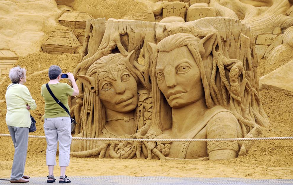 Două femei fotografiază o sculptură în nisip reprezentând actorii din filmul Avatar, în timpul festivalului Sculpturilor în nisip, în Blankenberg, marţi, 18 iunie 2013.