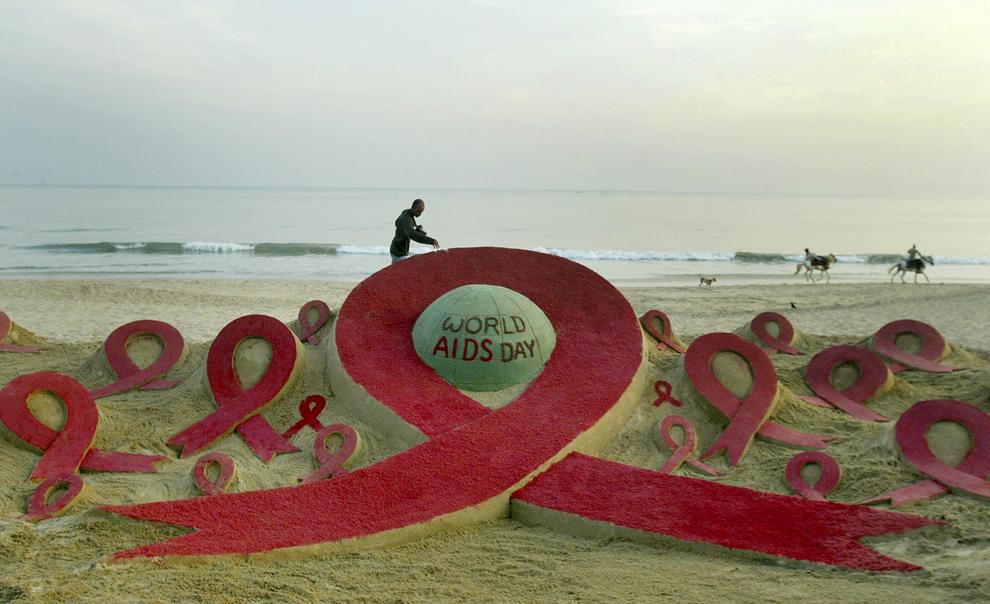 Un bărbat trece pe lângă o sculptură de nisip creată  de artistul Sudarshan Pattnaik în cadrul unei campanii de conştientizare a luptei împotriva HIV, pe plaja Puri, luni, 30 noiembrie 2009.