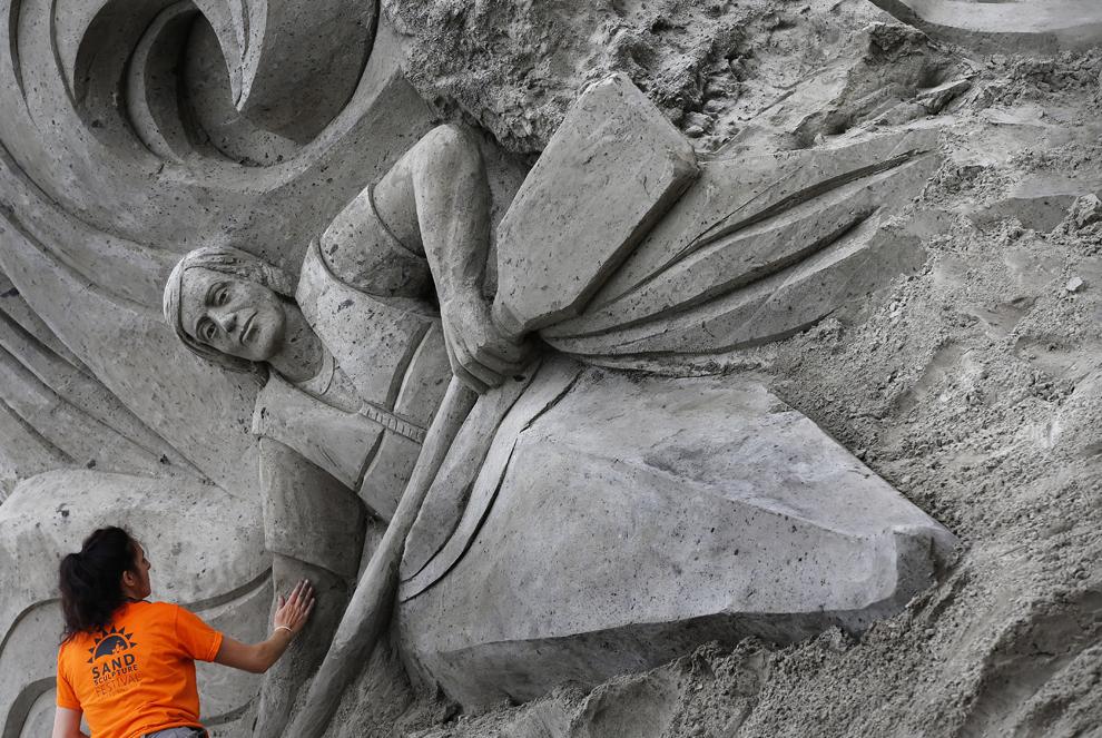 """Monserrat Cuest lucrează la o sculptură în nisip, intitulată """"Kayaking"""" în timpul festivalului Sculpturilor în nisip Friesland, în Sneek, Olanda, duminică, 30 iunie 2013."""