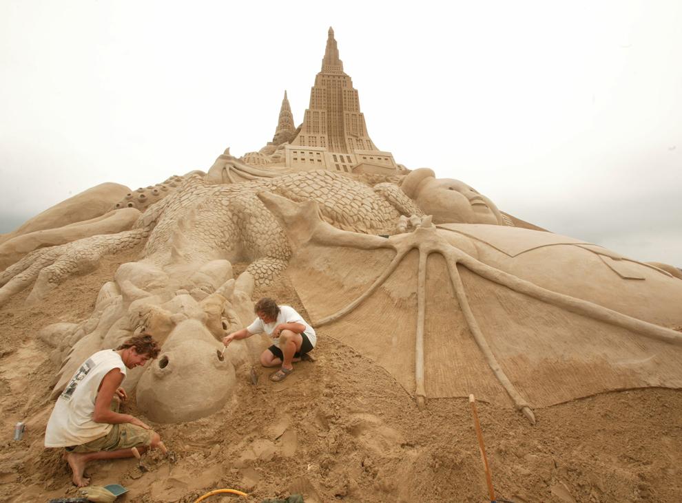 Două persoane lucrează la o sculptură în nisip în timpul festivalului Sculpturilor în nisip, în Zeebrugge, Belgia, joi, 15 iulie 2004.