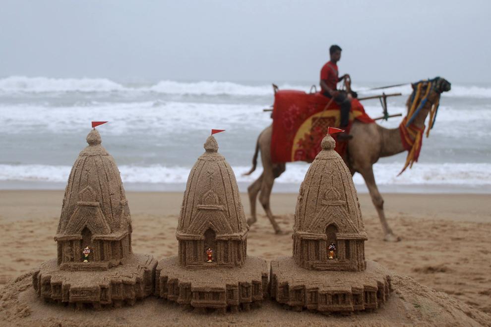 Un bărbat trece pe lângă sculpturi din nisip reprezentând miniaturi ale carelor de război ale zeitaţilor Hindu, create de artistul Sudersan Pattnaik, pe plaja Puri, miercuri, 20 iunie 2012.