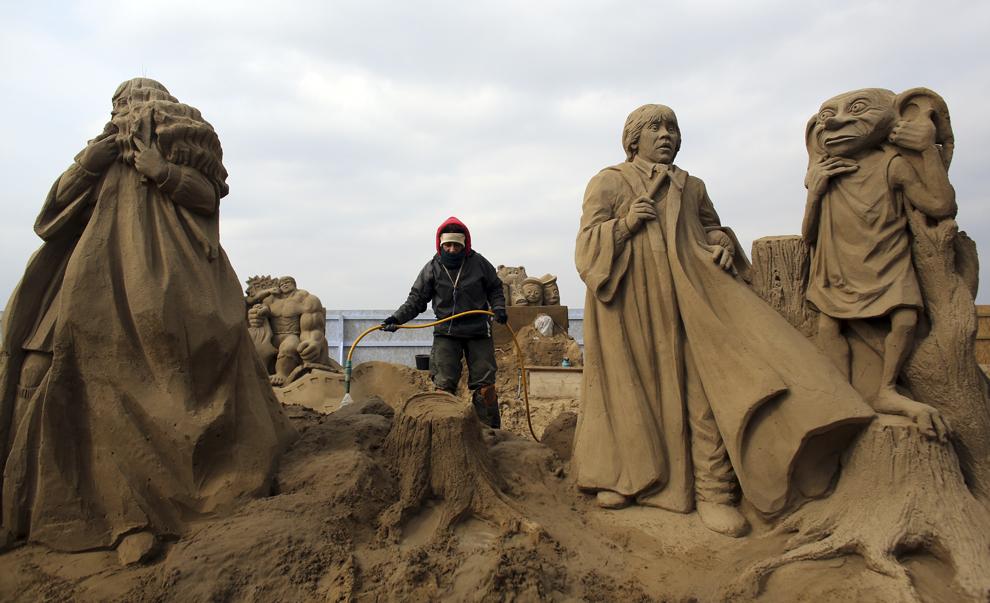 """Un bărbat lucrează la o sculptură în nisip cu tema """"Harry Potter"""" în timpul festivalului anual """"Weston-super-Mare Sand Sculpture festival"""", în Weston-Super-Mare, Anglia, marţi, 26  martie  2013."""
