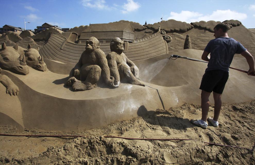 """Un bărbat  lucrează la o sculptură în nisip cu tema """"Once Upon a Time""""  în timpul festivalului anual """"Weston-super-Mare Sand Sculpture festival"""", în Weston-Super-Mare, Anglia, miercuri, 16 aprilie 2014."""