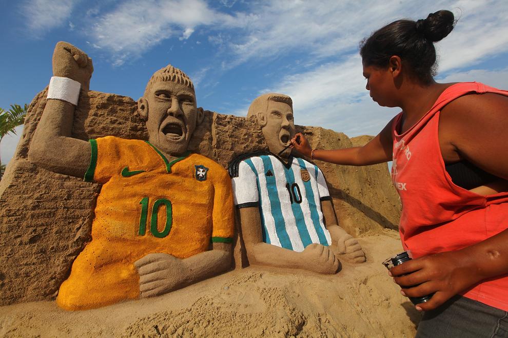 O femeie pictează o sculptură în nisip reprezentând jucatorii de fotbal Neymar şi Messi, pe plaja Copacabana, în Rio de Janeiro, Brazilia, duminică, 1 iunie 2014.