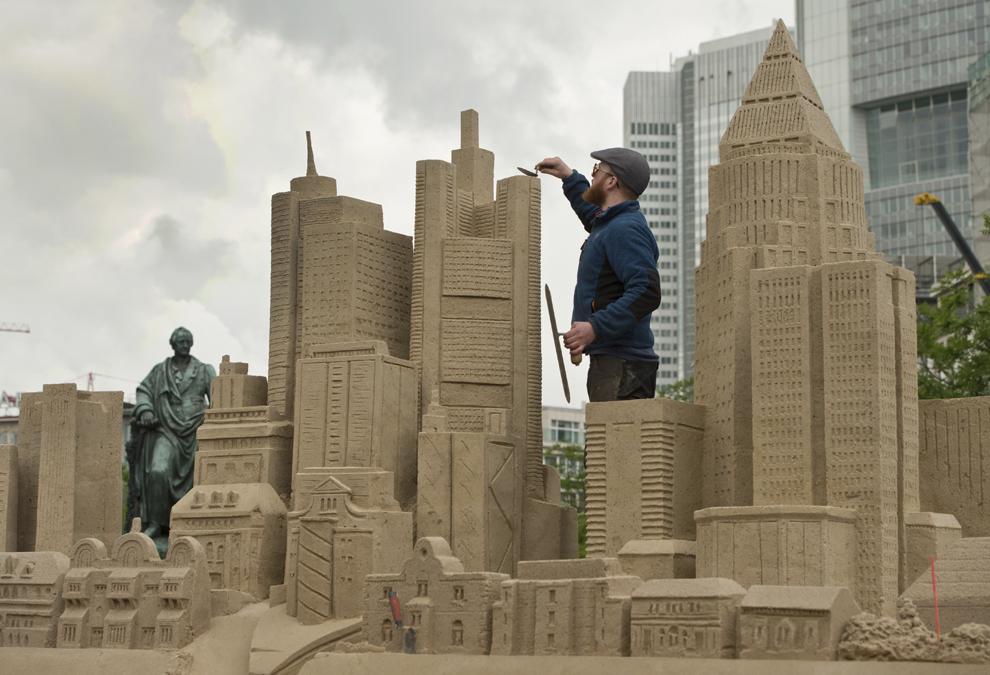 Un bărbat  lucrează la o sculptură în nisip, în Frankfurt, Germania, vineri, 24 mai 2013.