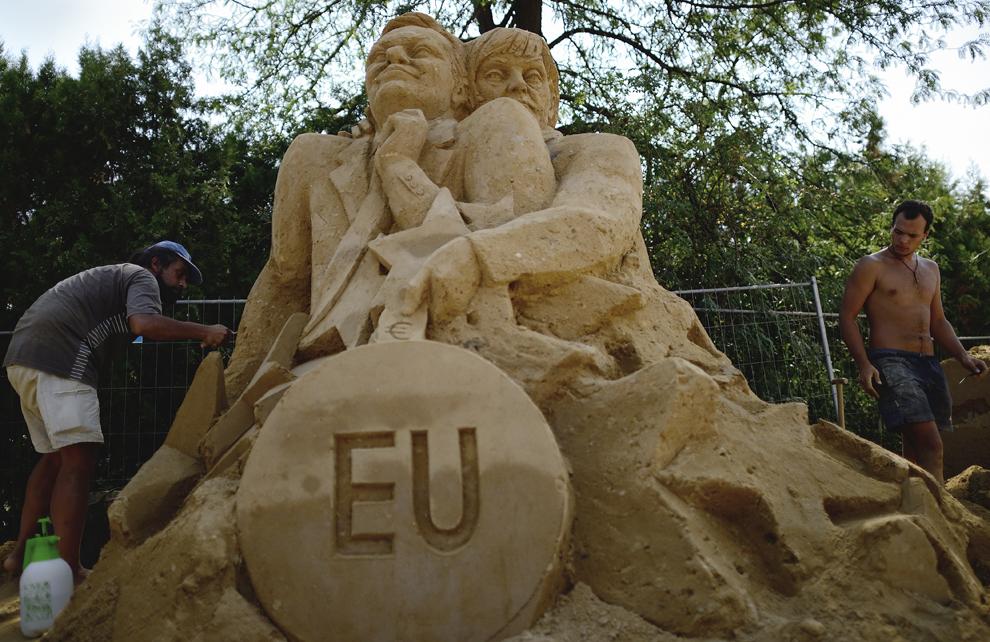 Sculptorul bulgar Daniel Kanev (S) lucrează la o sculptură în nisip înfăţişându-i pe Preşedintele Comisiei Europene, Jose Manuel Barroso şi cancelarul german, Angela Merkel, în timpul festivalului sculpturilor în nisip, în Sofia, Bulgaria, luni, 26 august 2013.