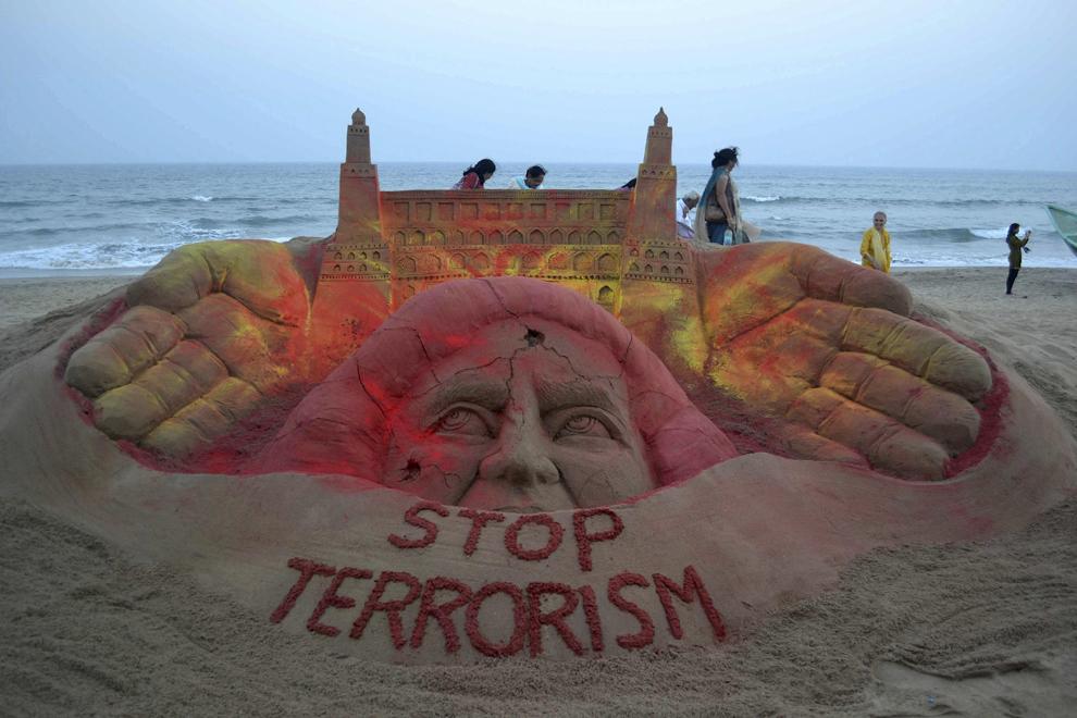 """Persoane trec pe lângă o sculptură din nisip cu mesajul """"Opriţi Terorismul"""", creată  de artistul Sudersan Pattnaik, pe plaja Puri din India, vineri, 22 februarie 2013."""