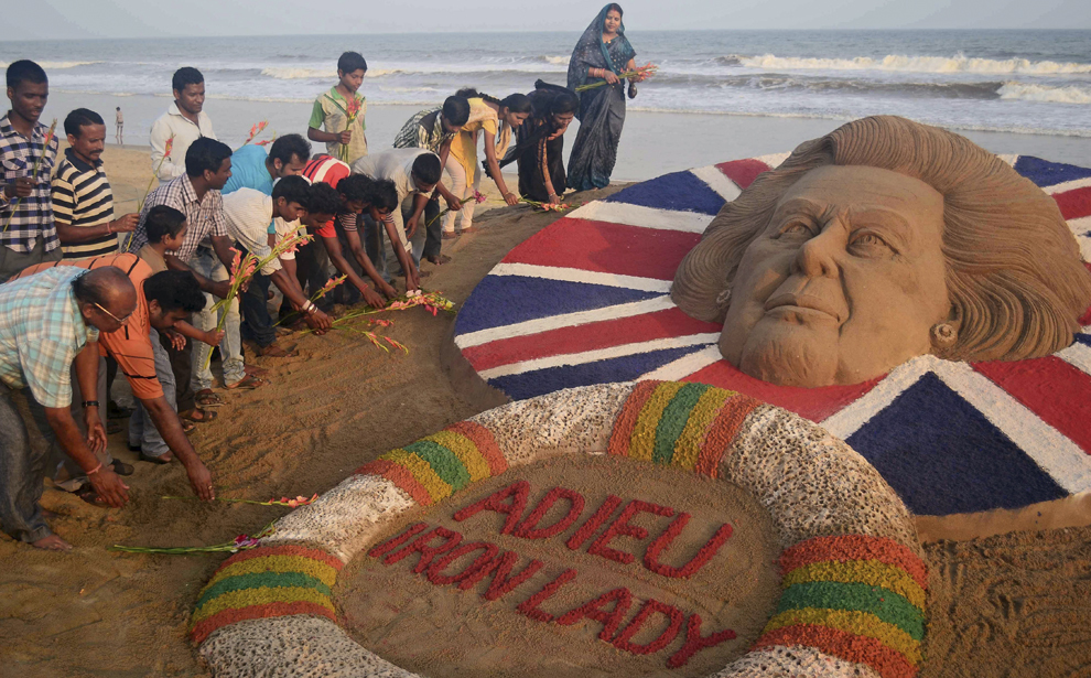 Indieni lasă flori în semn de omagiu lângă o sculptură de nisip înfăţişându-l pe fostul prim-ministru al Marii Britanii, Margaret Thatcher, creată de artistul Sudersan Pattnaik pe plaja Puri din India, marţi, 9 aprilie 2013.