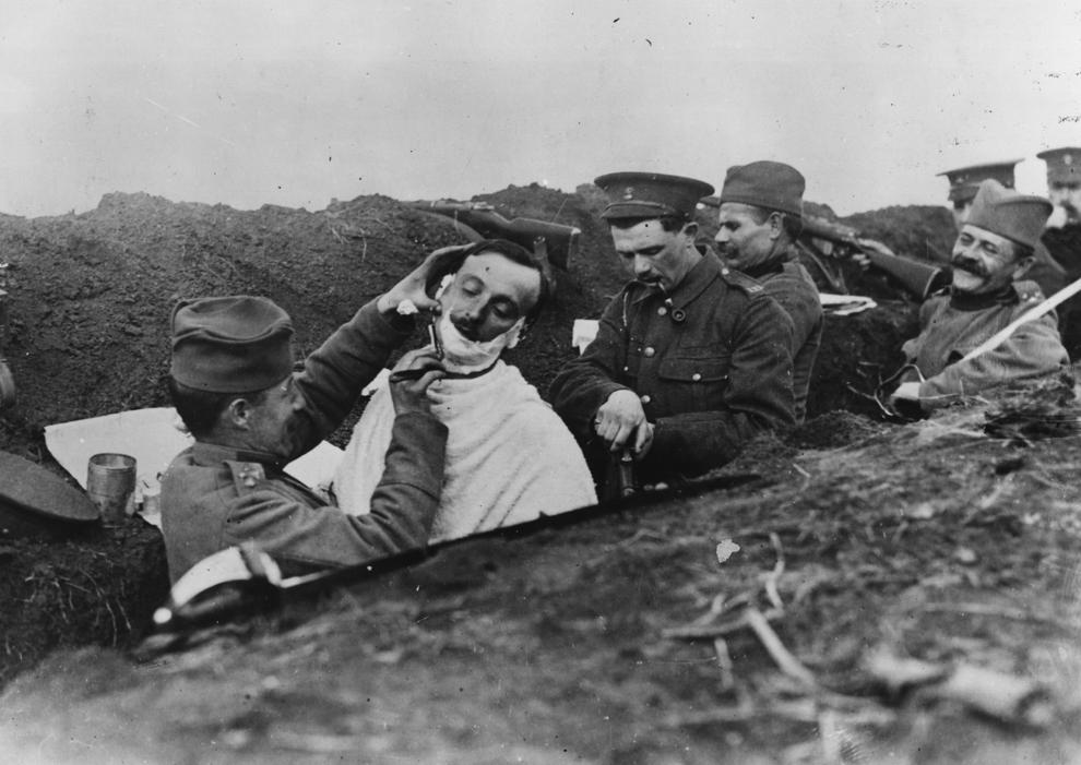 Un soldat este bărbierit în tranşeele sârbe, circa 1916.