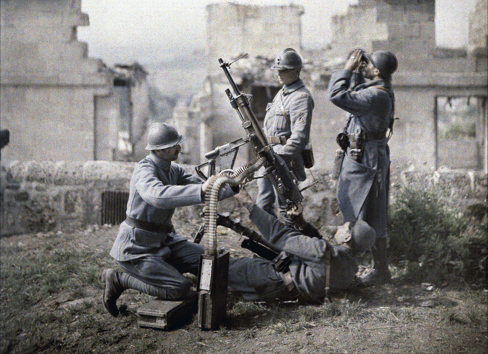 Soldaţi francezi ce manevrează o mitralieră stau printre ruine, în timpul bătăliei de la Aisne, Franţa, Frontul de Vest, în timpul Primului Război Mondial, circa 1917. Fotografie color: (Autochrome Lumière) de Fernand Cuville (1887-1927).