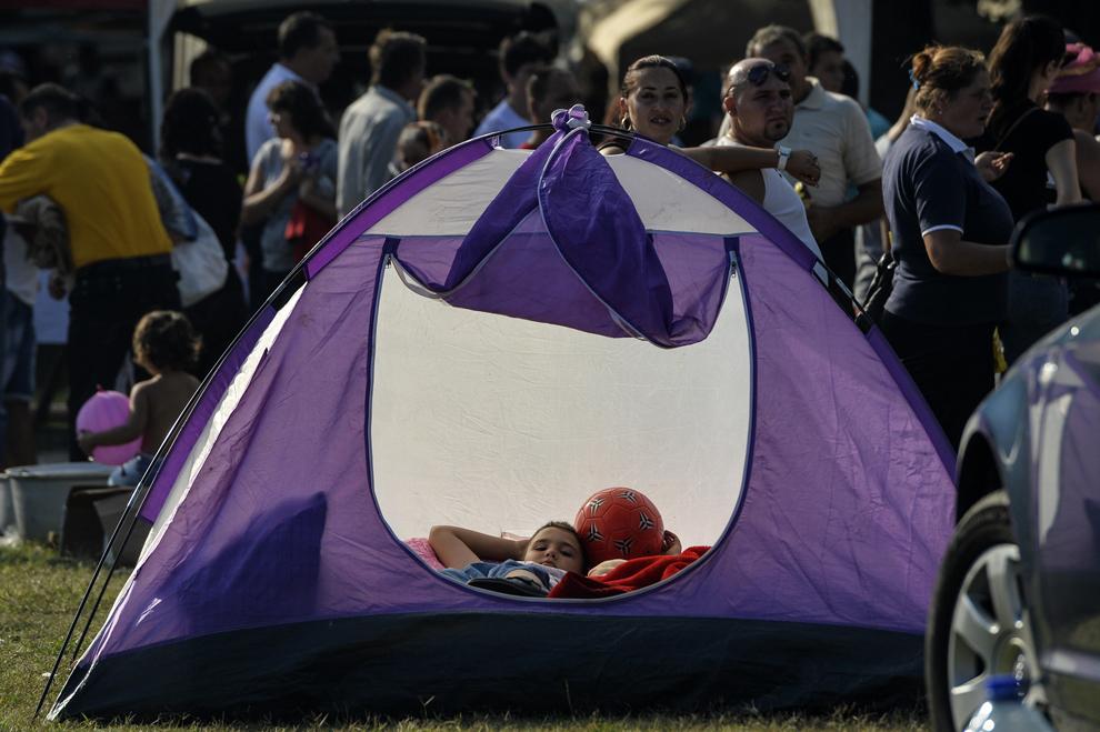 Un copil de etnie romă se odihneşte într-un cort, în timpul reuniunii anuale a romilor, cu ocazia sărbătorii Naşterii Maicii Domnului, în Costeşti, Vâlcea, luni, 8 septembrie 2014.
