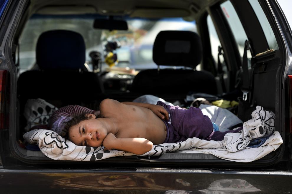 Un copil de etnie romă se odihneşte într-o maşină, în timpul reuniunii anuale a romilor, cu ocazia sărbătorii Naşterii Maicii Domnului, în Costeşti, Vâlcea, luni, 8 septembrie 2014.