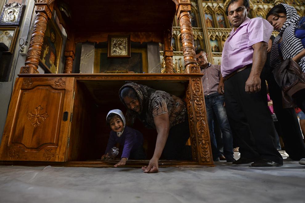 Mai mulţi romi de naţionalitate română stau la rând lângă icoane ortodoxe, pentru a trece pe sub o masă, în timp ce participă la un serviciu religios, cu ocazia reuniunii anuale a romilor, cu ocazia sărbătorii Naşterii Maicii Domnului, în Costeşti, Vâlcea, luni, 8 septembrie 2014.