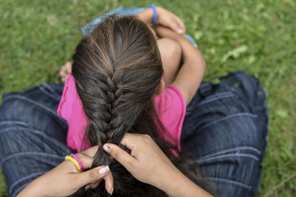O femeie împleteşte părul unei fetiţe de etnie romă, în timpul reuniunii anuale a romilor, cu ocazia sărbătorii Naşterii Maicii Domnului, în Costeşti, Vâlcea, luni, 8 septembrie 2014.