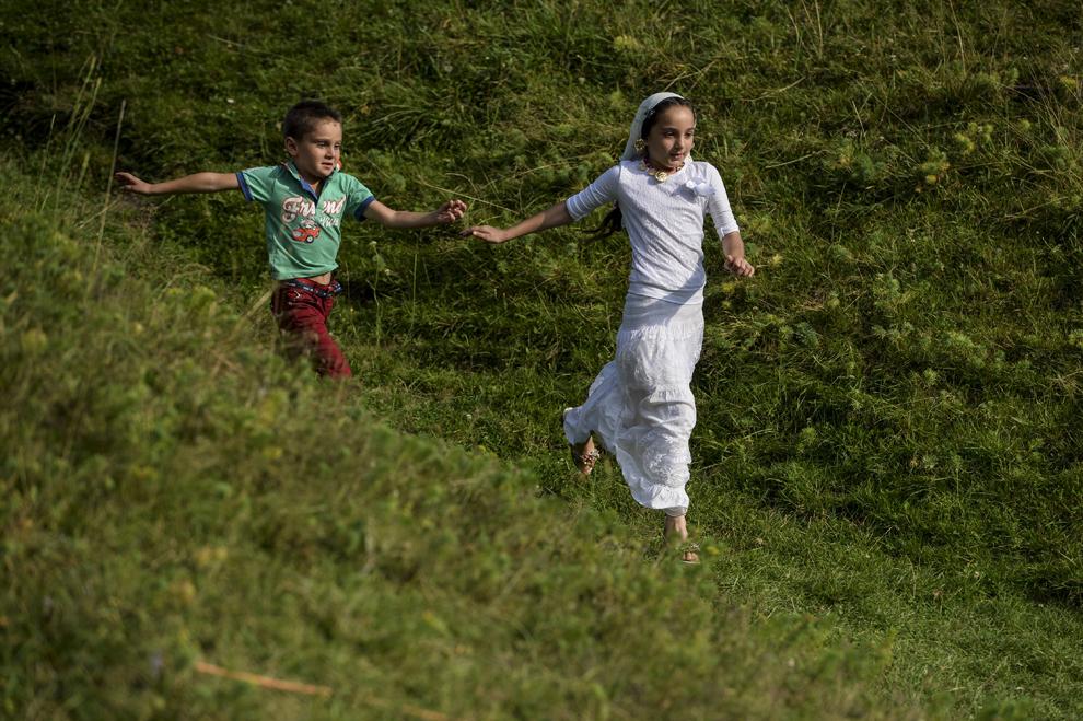 Doi copii de etnie romă aleargă, în timpul reuniunii anuale a romilor, cu ocazia sărbătorii Naşterii Maicii Domnului, în Costeşti, Vâlcea, luni, 8 septembrie 2014.