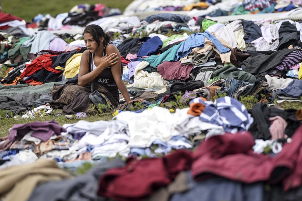 O fată de etnie romă stă langă mai multe gramezi cu haine second hand aduse pentru a fi vândute în timpul reuniunii anuale a romilor, cu ocazia sărbătorii Naşterii Maicii Domnului, în Costeşti, Vâlcea, luni, 8 septembrie 2014.